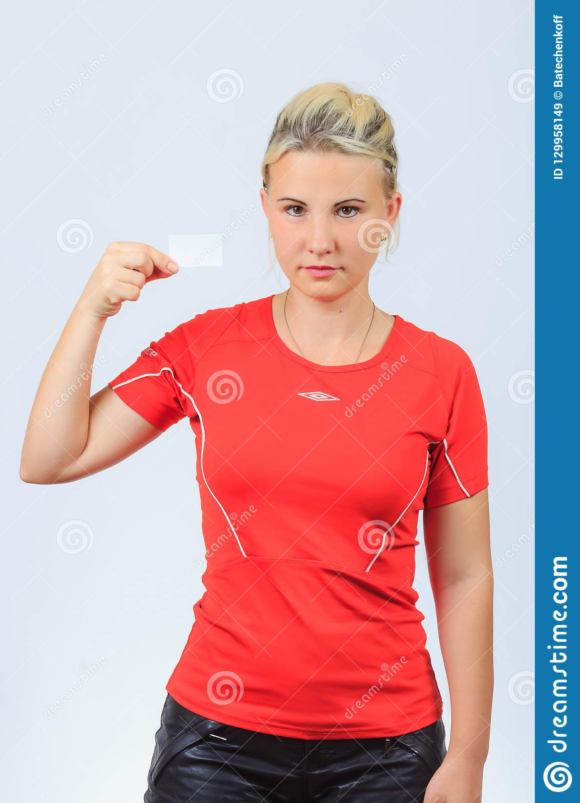 b7ca8b4d Young serious blonde girl in red shirt and black shorts holds blank  business card with copyspace near face