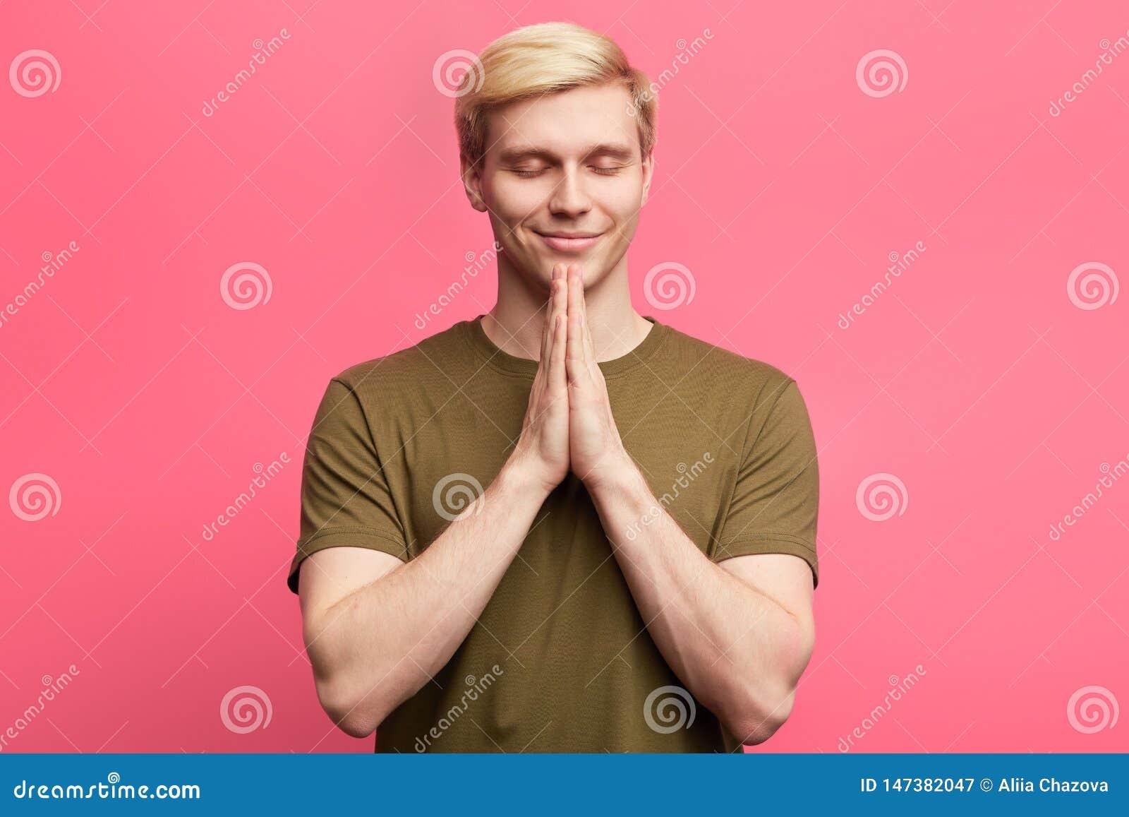 Young blonde guy puts hands together in prayer or meditation