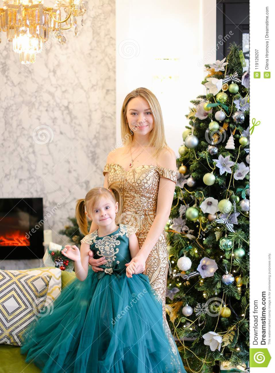 young blonde mother and little daughter wearing dresses standing