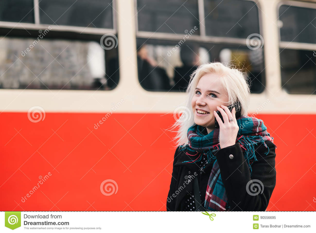 Young blonde smiling girl talking on the phone on a background of red train. Outdoor portrait of a girl.