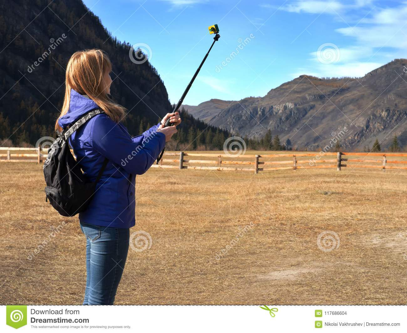Young blonde woman backpacker taking photo with action camera on mountain peak.