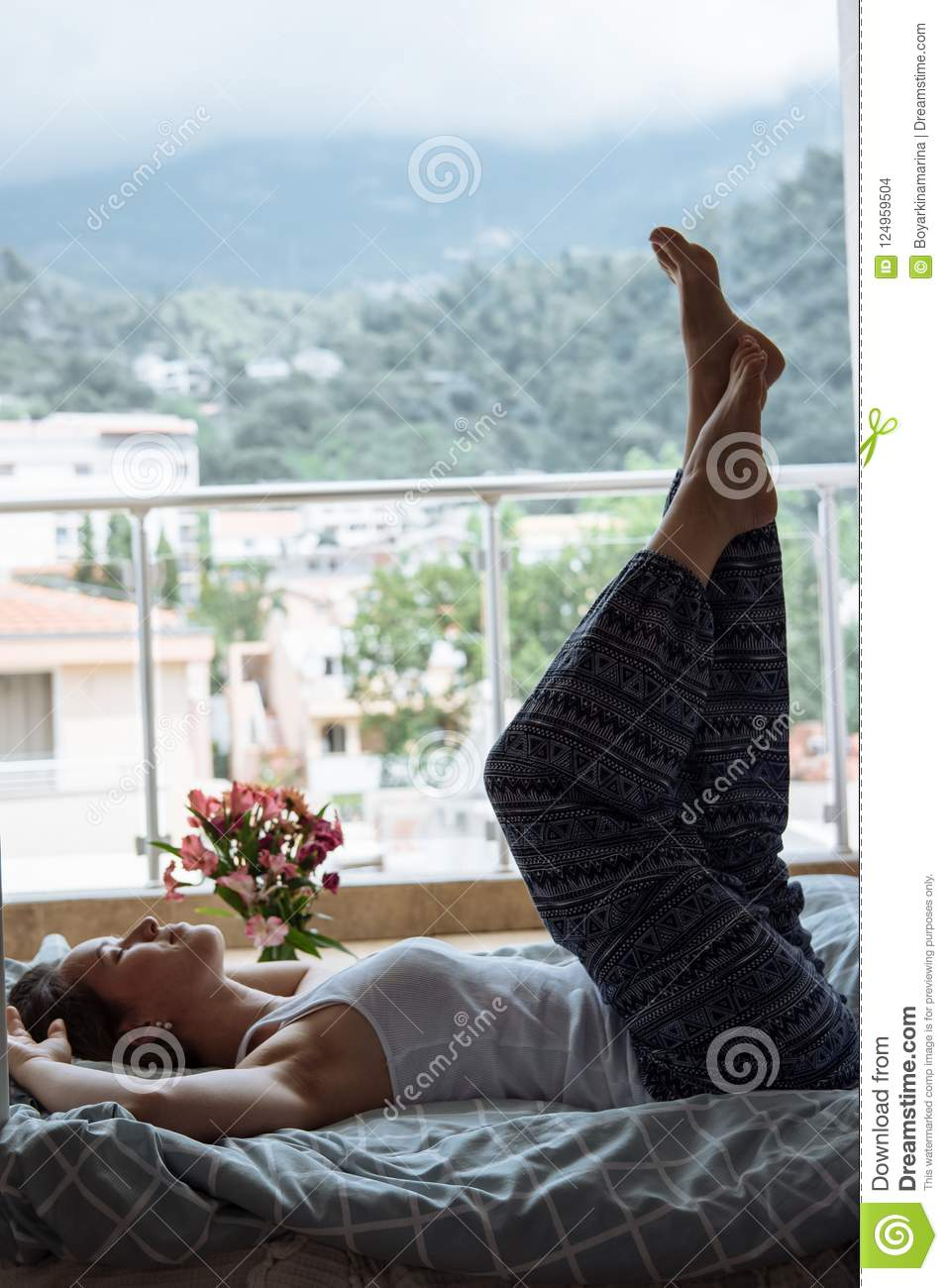 Young Blonde woman in blue pajamas on the bed having lazy morni