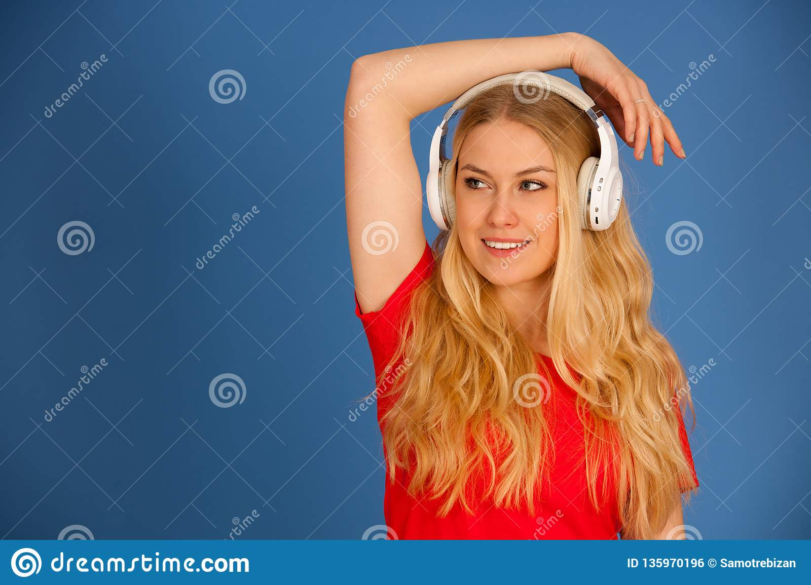 Young blonde woman with headphones listens to the music over blue background