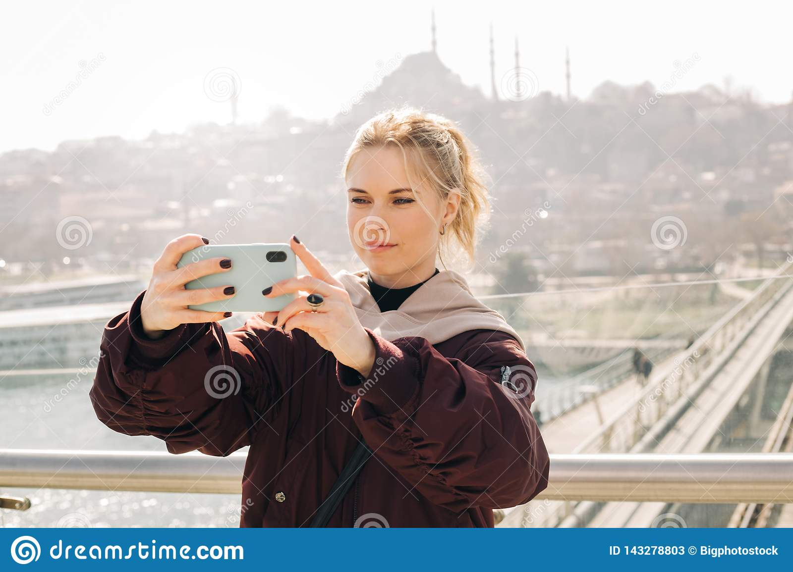 Young blonde woman in jacket makes selfie against background of glass window.