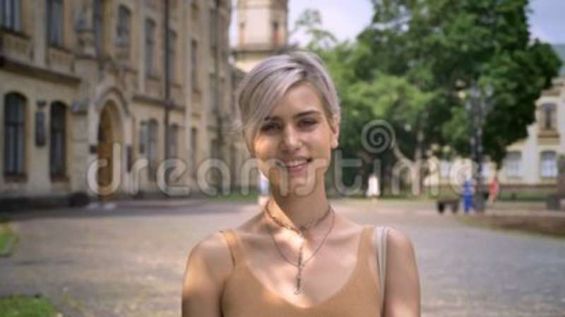 Young Blonde Woman With Short Haircut Looking At Camera And Smiling