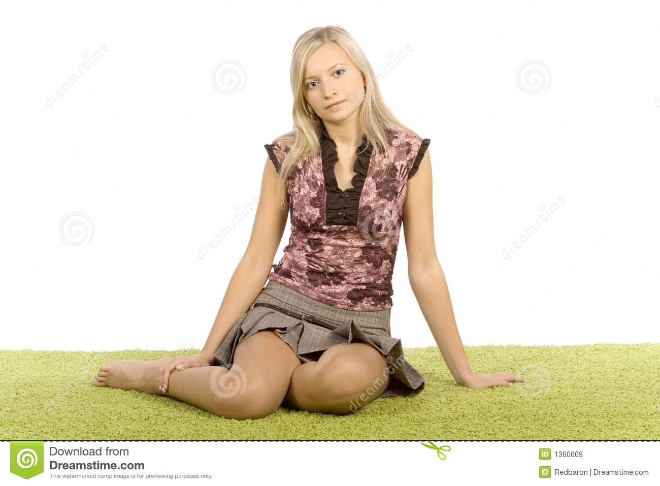 Young blonde woman sitting on the green carpet