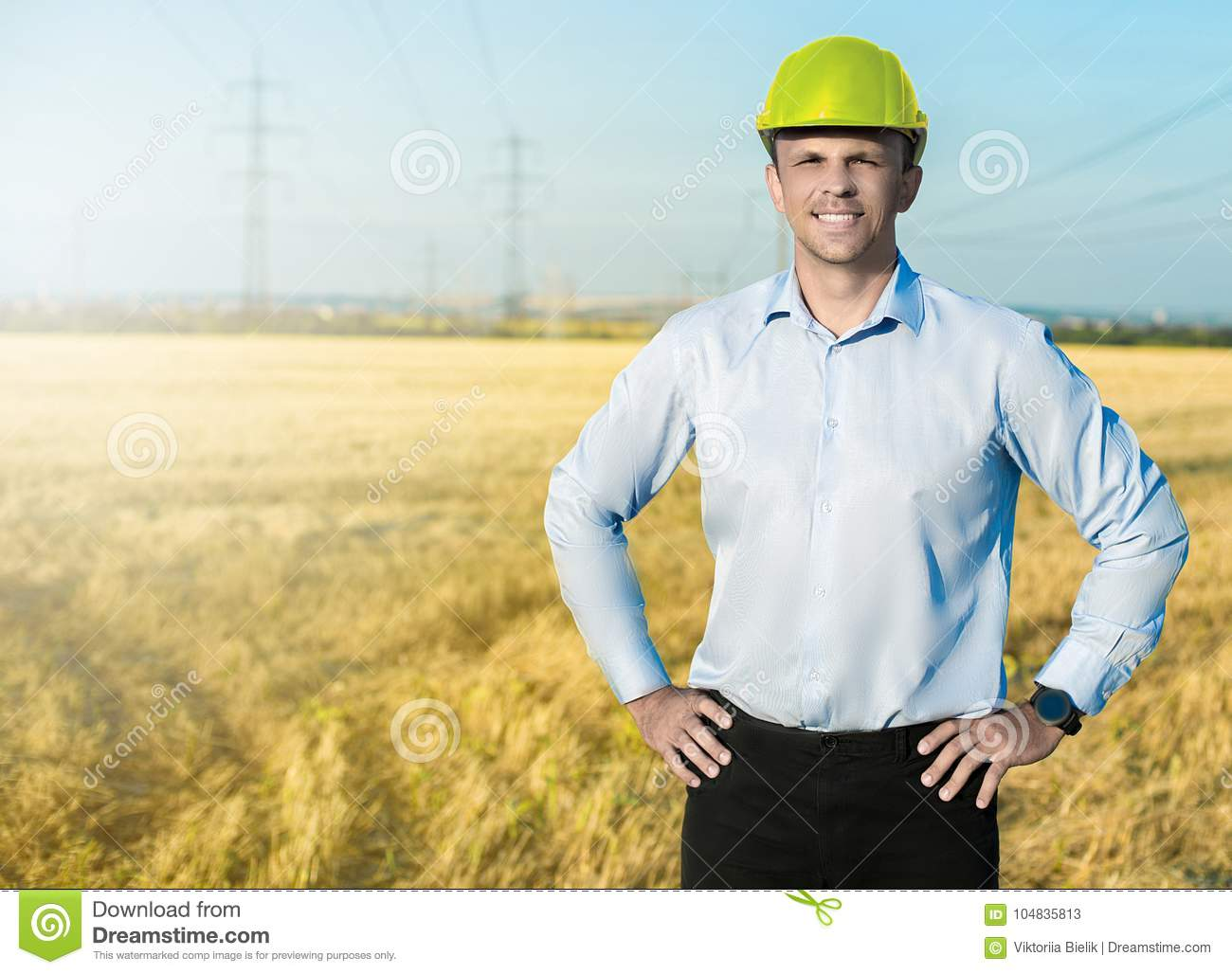 Young blue collar worker or engineer wearing in yellow helmet stands in the field with wide smile.
