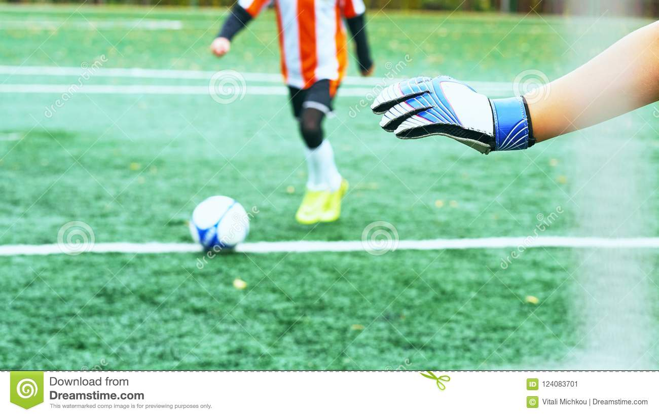 Young blurred soccer player taking a penalty kick against goal net.