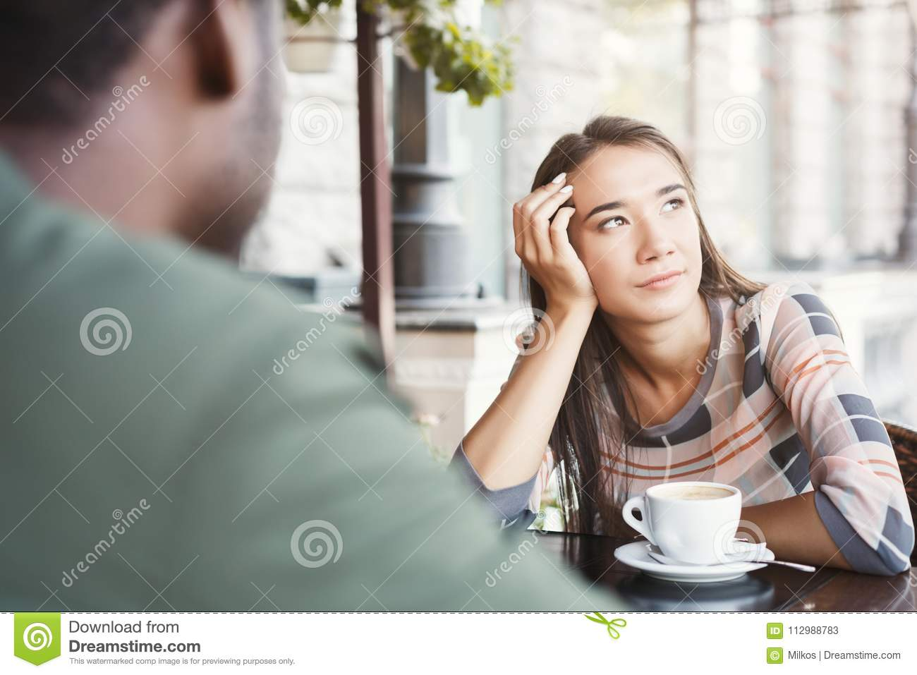 Young bored girl drinking coffee on date at a cafe