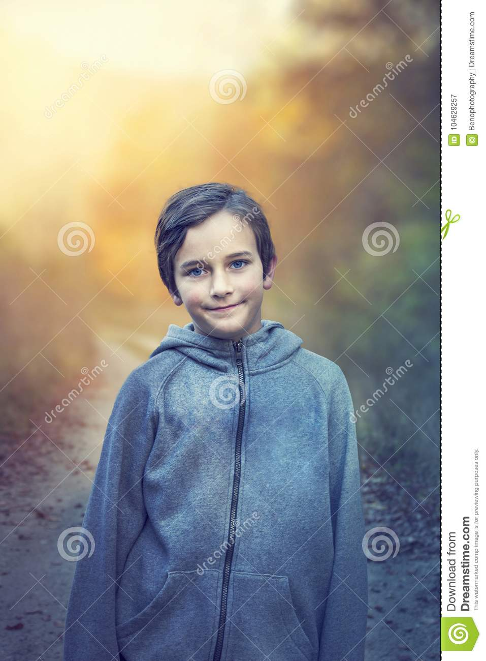 Young Boy With Blue Eyes Walking In Forest On Sunset Portrait O
