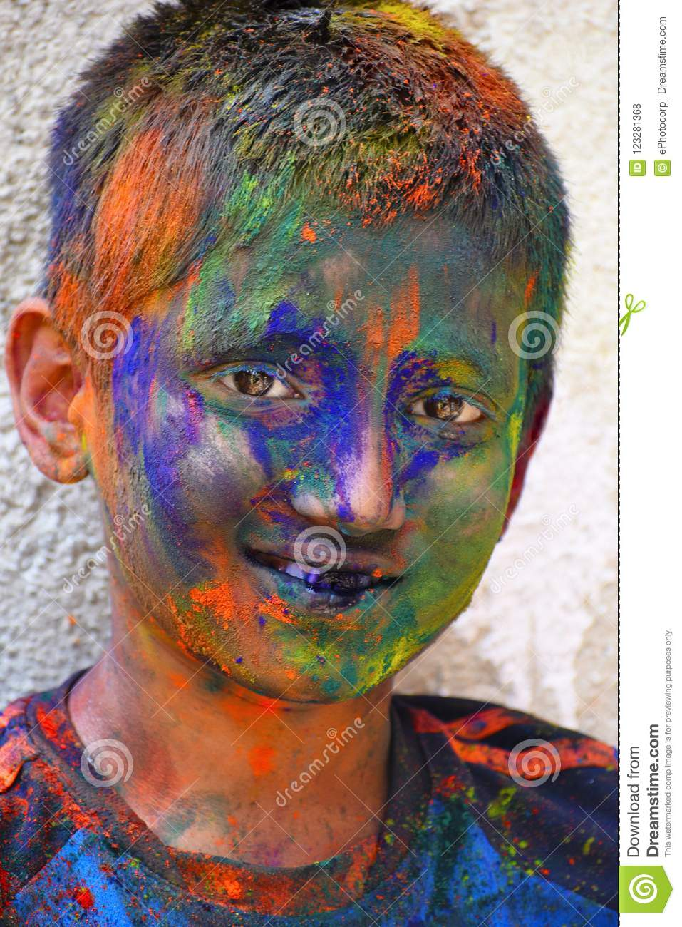 Young boy celebrating of Holi festival with colored powder on face, Yerawada