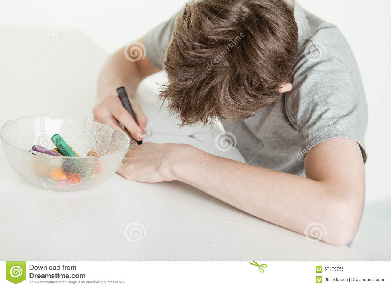 Young Boy Coloring His Drawing Using Crayons Stock Photo