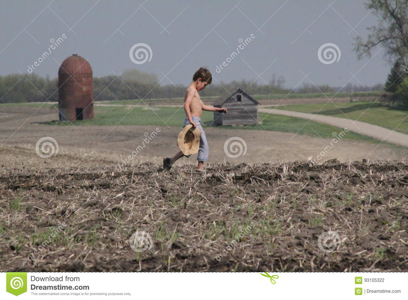 Young boy crosses field carrying straw hat