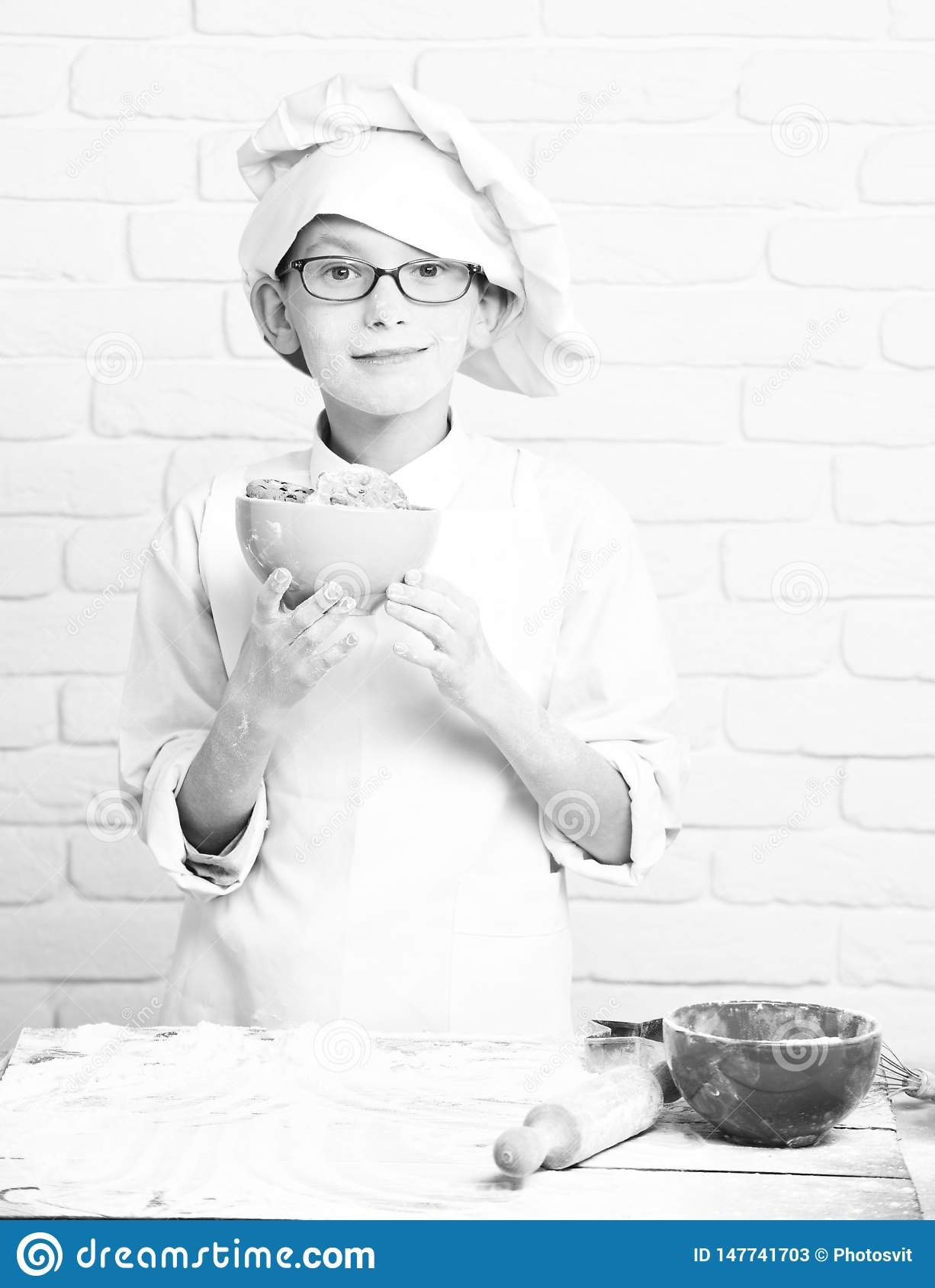Young boy cute cook chef in white uniform and hat on stained face flour with glasses standing near table with rolling