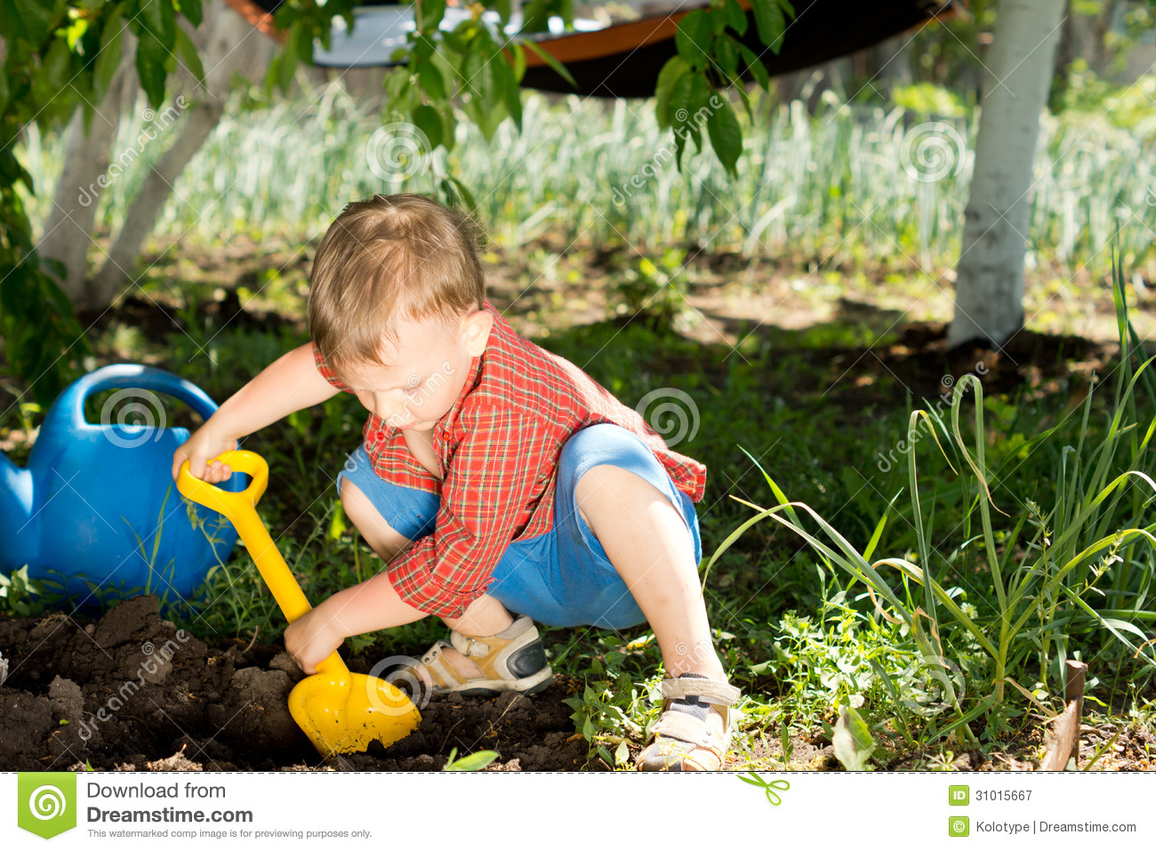 Digging Toys For Boys : Young boy digging in the garden stock image
