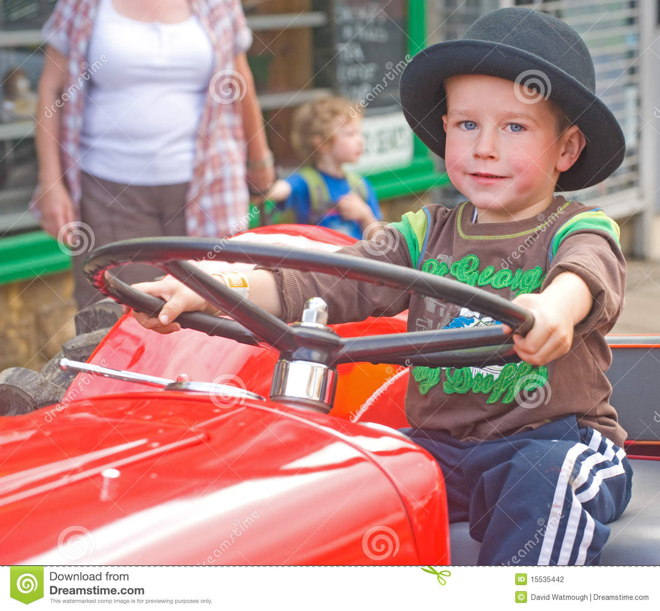 A young boy  driving  a red tractor.