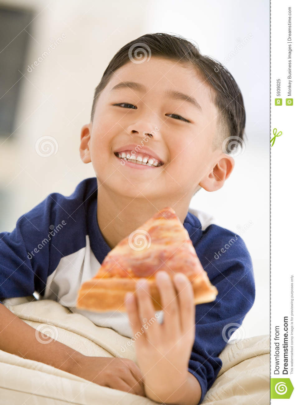 Young boy eating pizza slice in living room