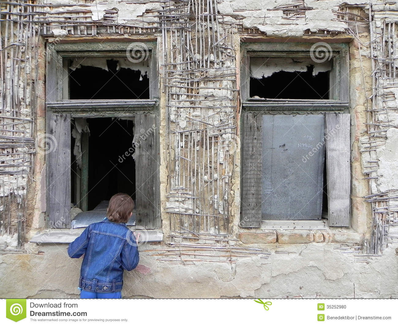 Young boy in front of an old window