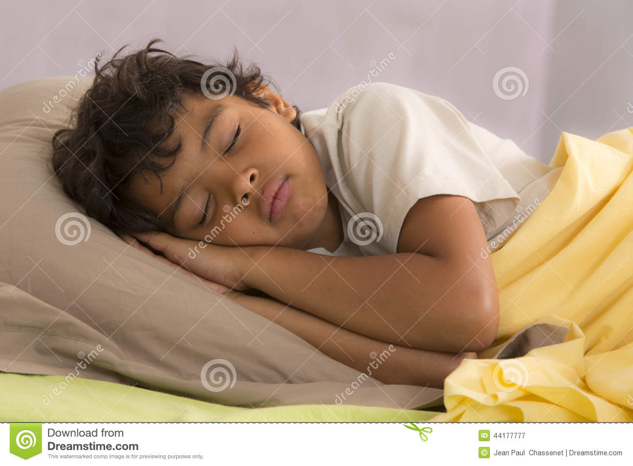Young boy fully sleeping in his bed