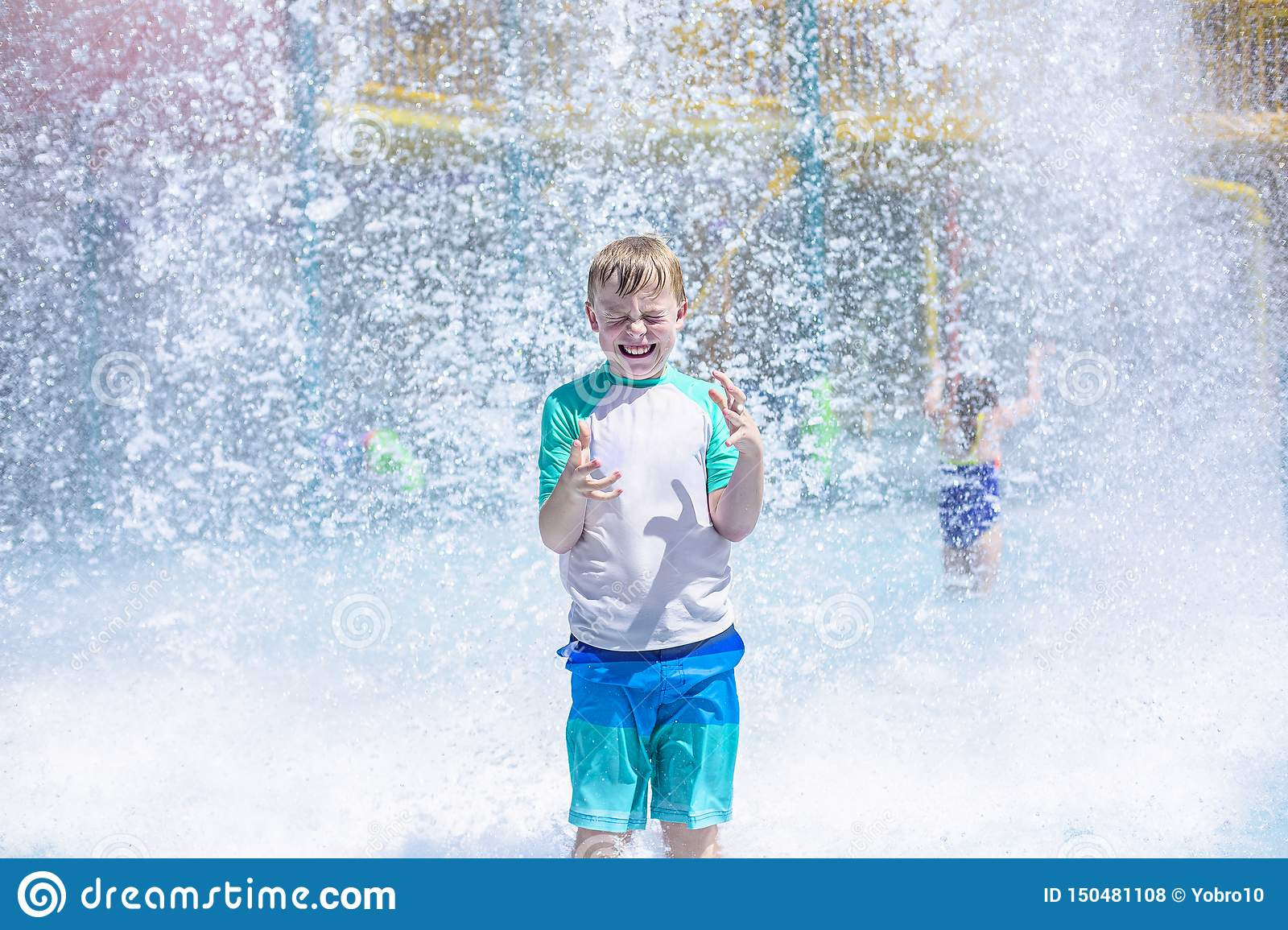 Young boy getting soaking wet while at an outdoor water park