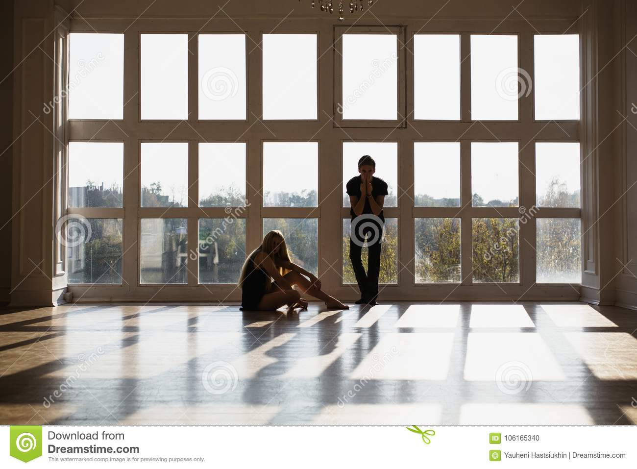A young boy and girl with long blond hair standing in front of the window. Dancers during a workout.