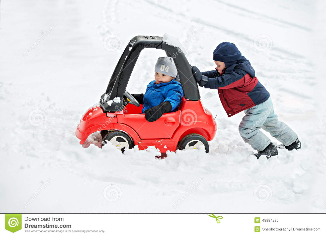 Young Boy Gives a Push to his Brother s Car Stuck in the Snow