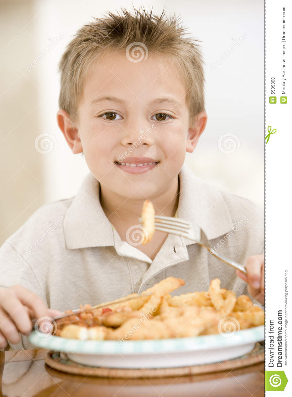 Young boy indoors eating fish and chips stock photo for Dreaming of eating fish