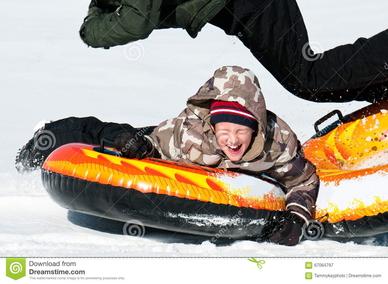 04640969c Young Boy Laughing On A Snow Tube Stock Image - Image of nature ...