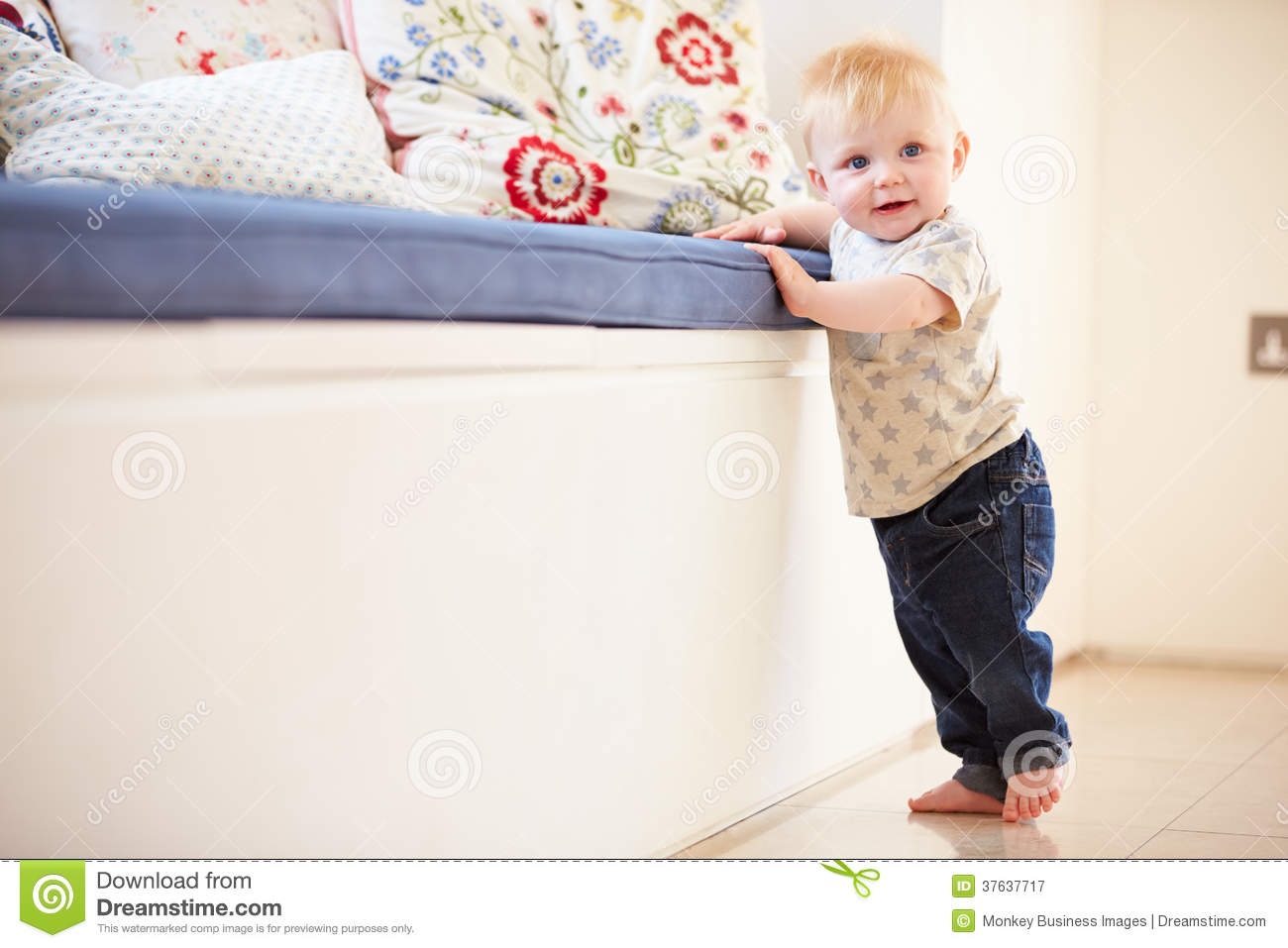 Young Boy Learning To Walk By Holding Onto Furniture