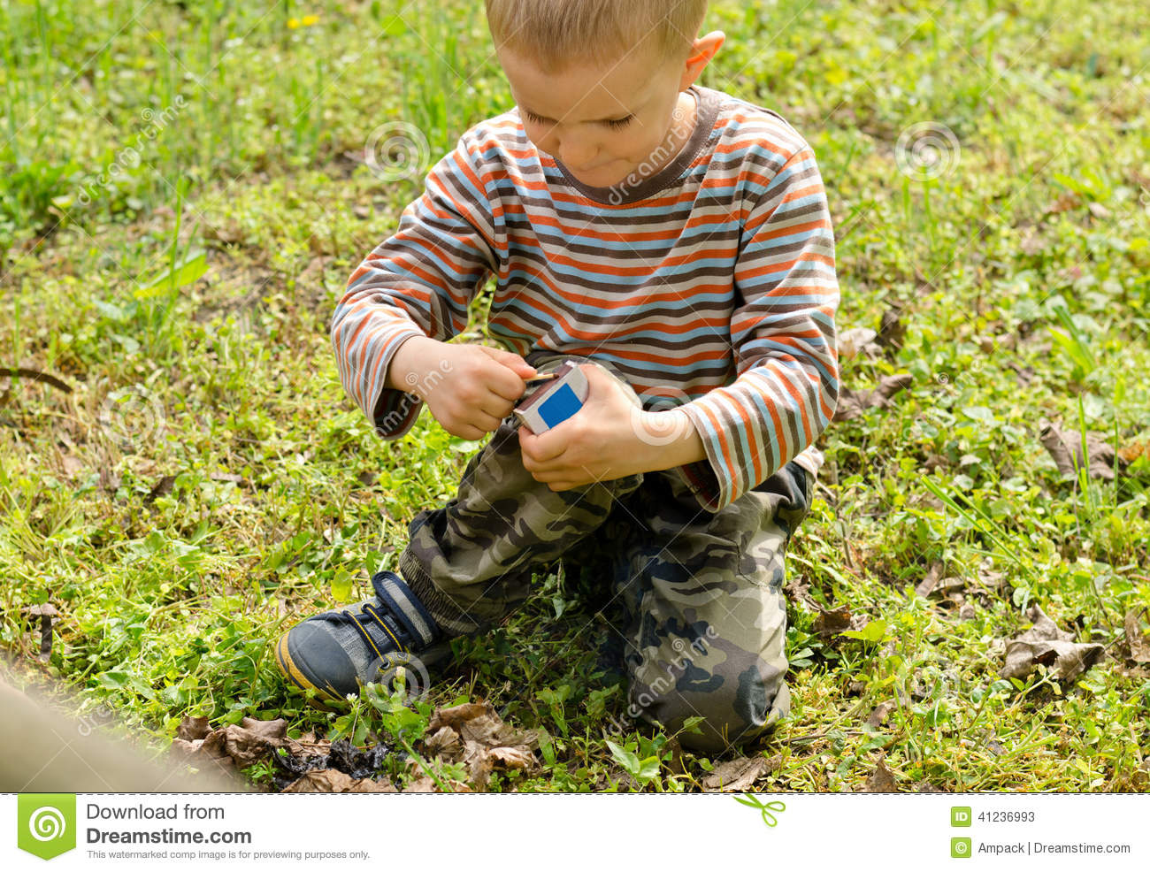 Young boy lighting a fire outdoors