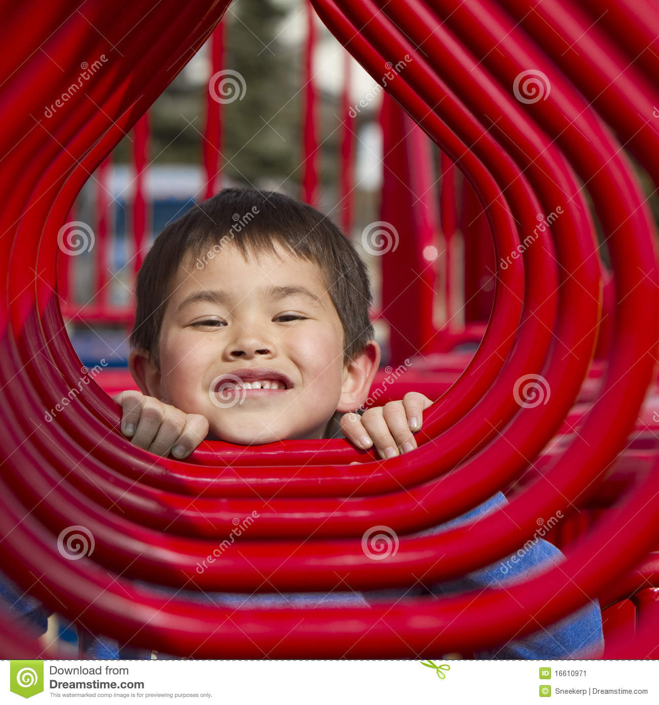 Young boy looking in the hoops of a playground