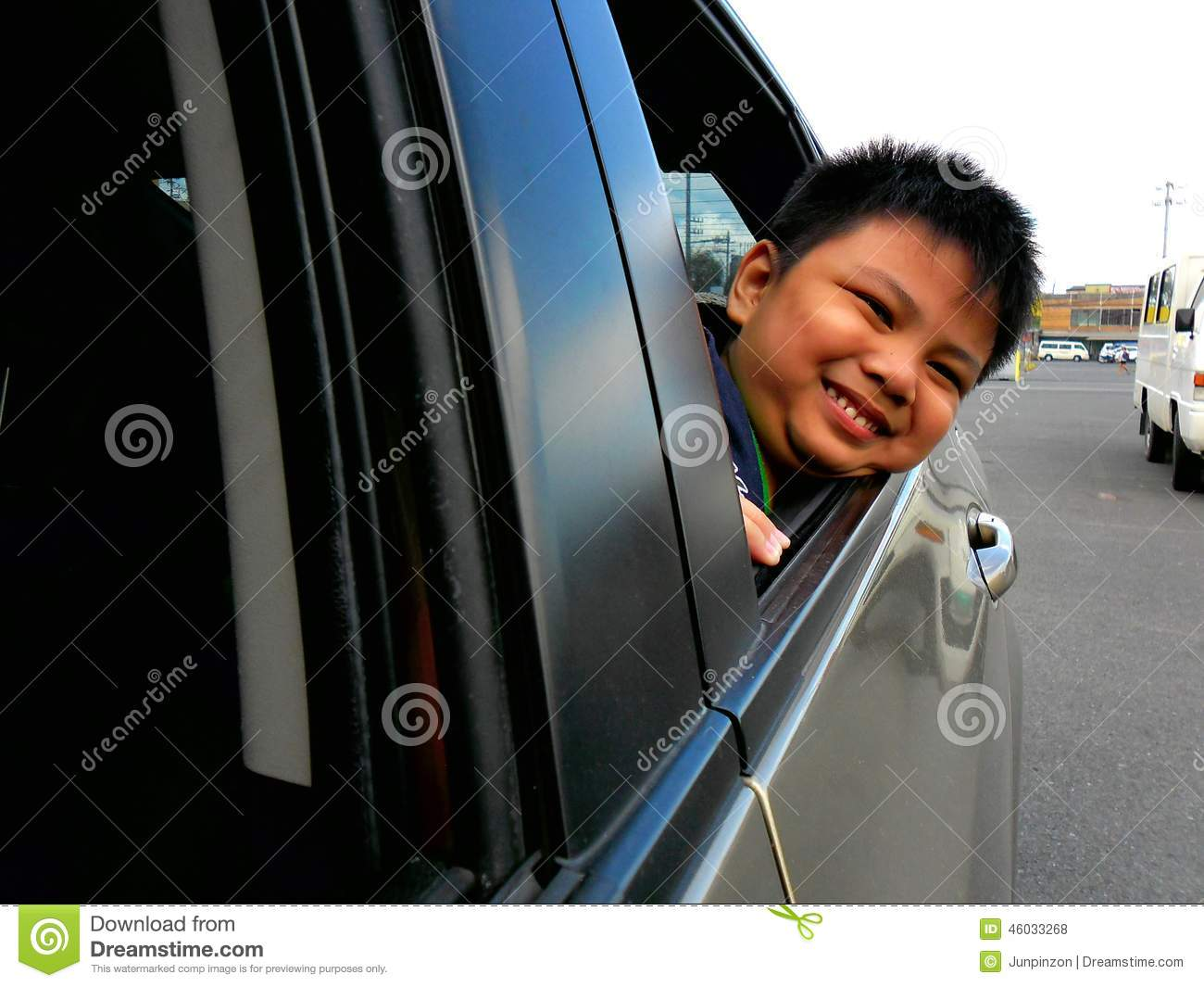 young boy peeking or looking out a car window stock photo