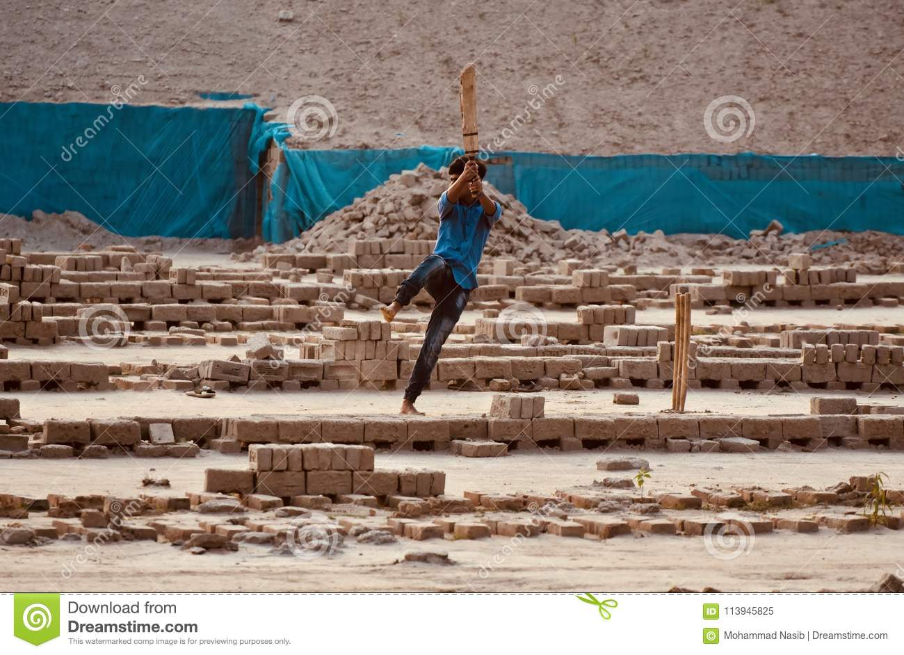 Young boy is playing cricket around a bricks field in Bangladesh