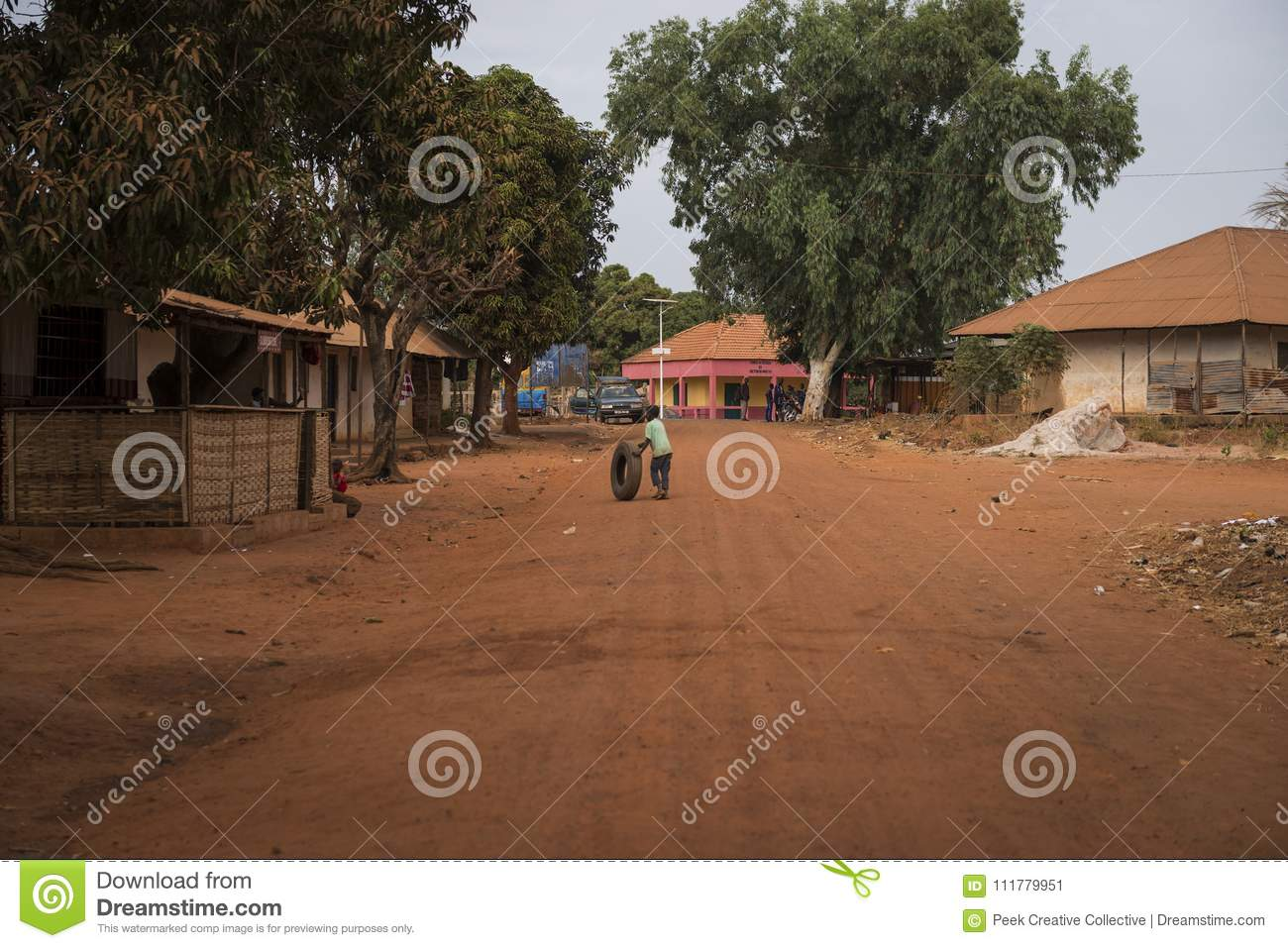 Young boy playing with an old tire in a dirt road in the town of Nhacra in Guinea Bissau, West Africa