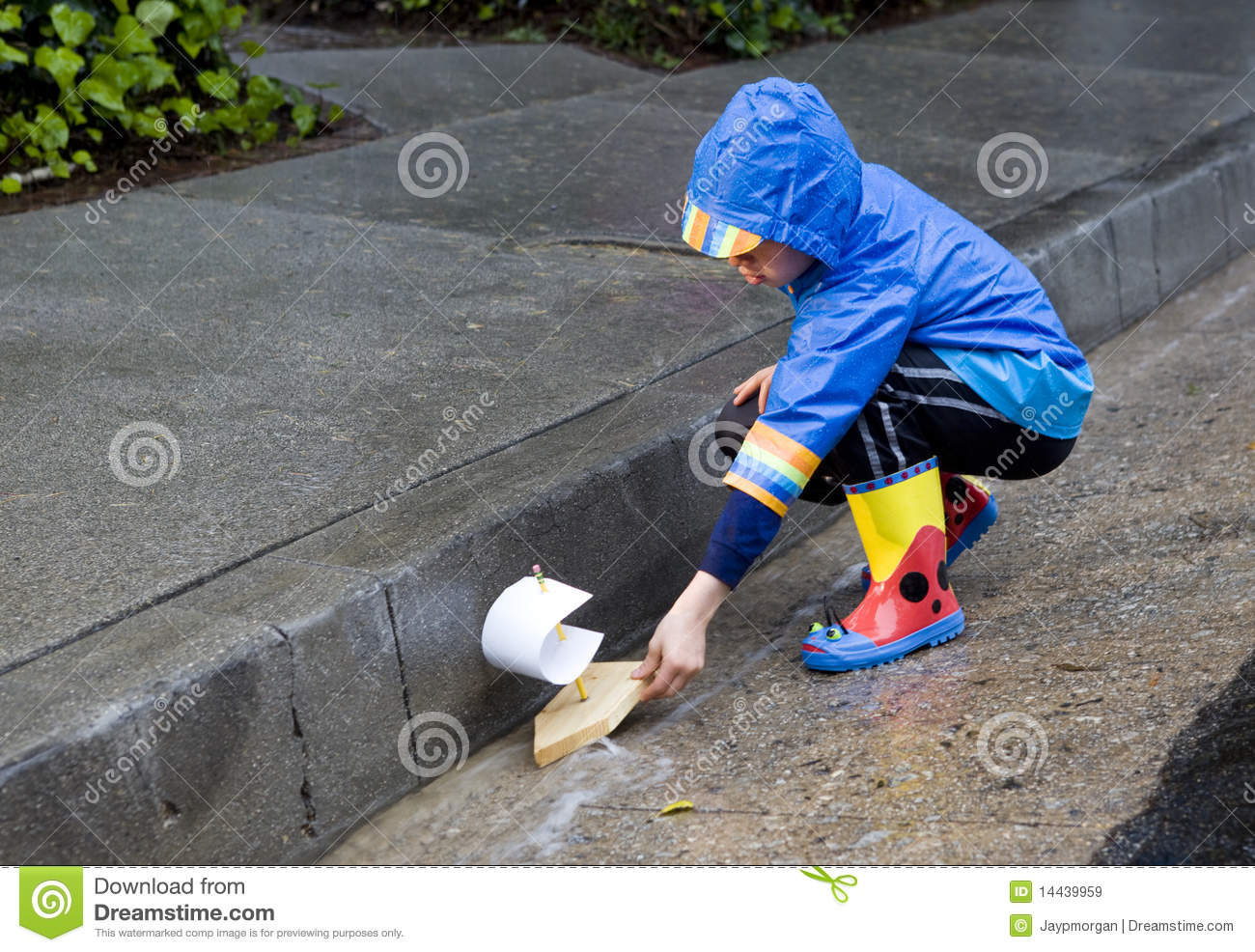 Lillle Boy Toys Boats : Young boy playing with toy boat in the rain stock image