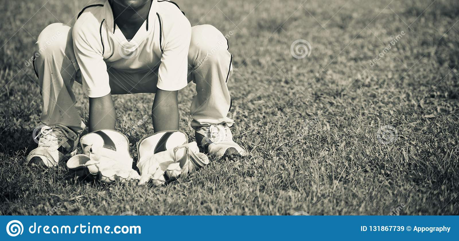 Young boy practicing wicket keeping around a field