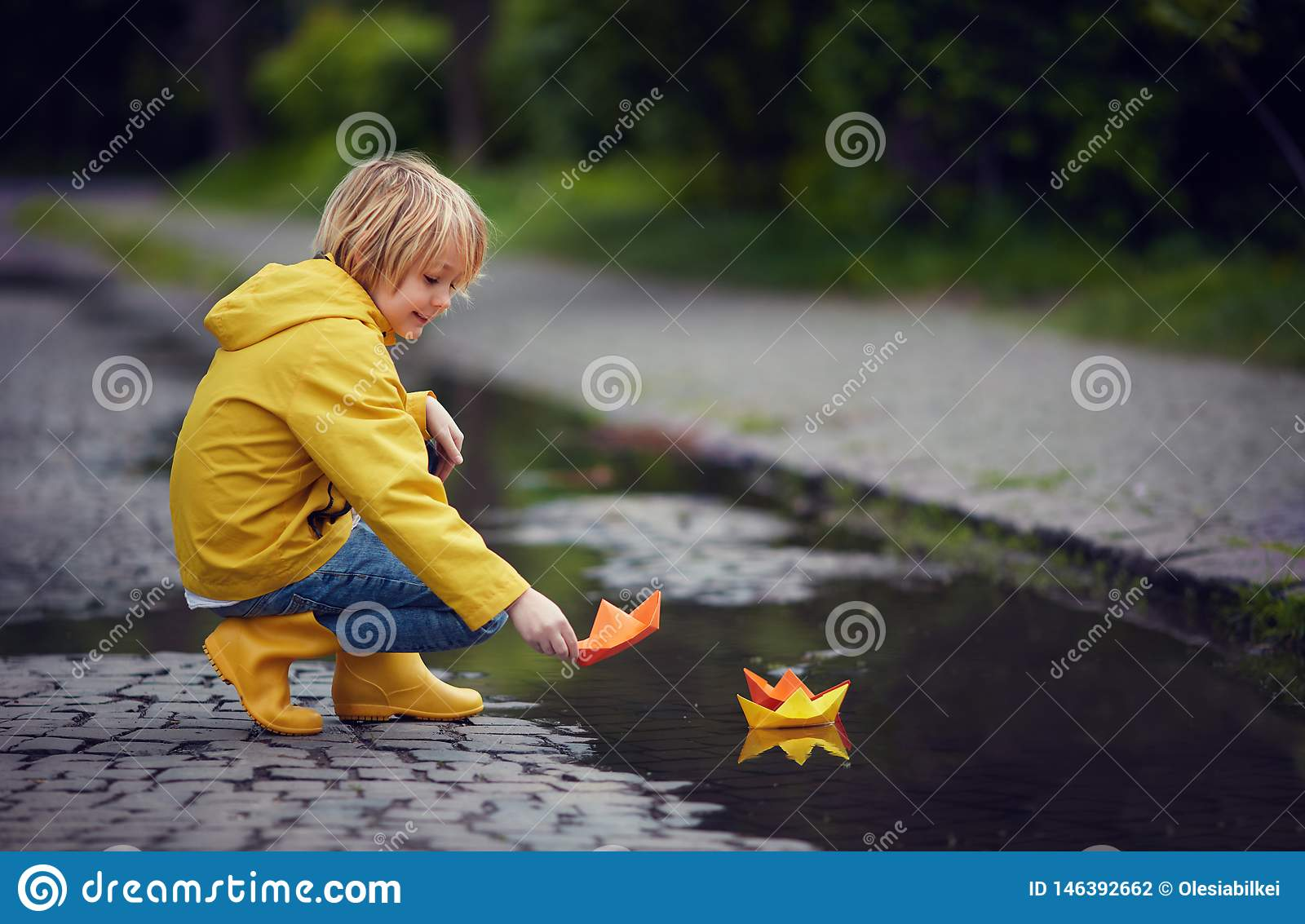 Young boy in rain boots and coat is putting paper boats on the water, at spring rainy day