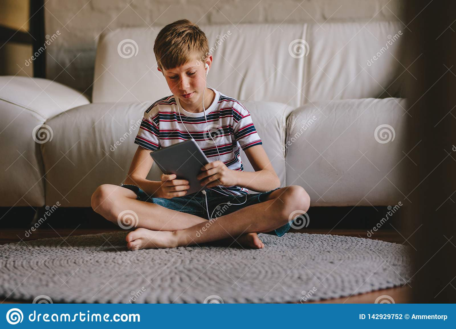 Boy playing online game on tablet at home
