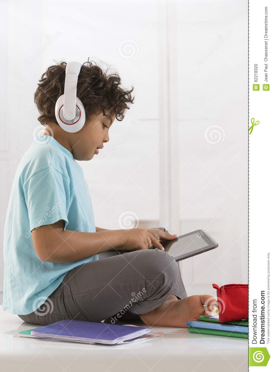 Young boy sitting at home, listen to music and