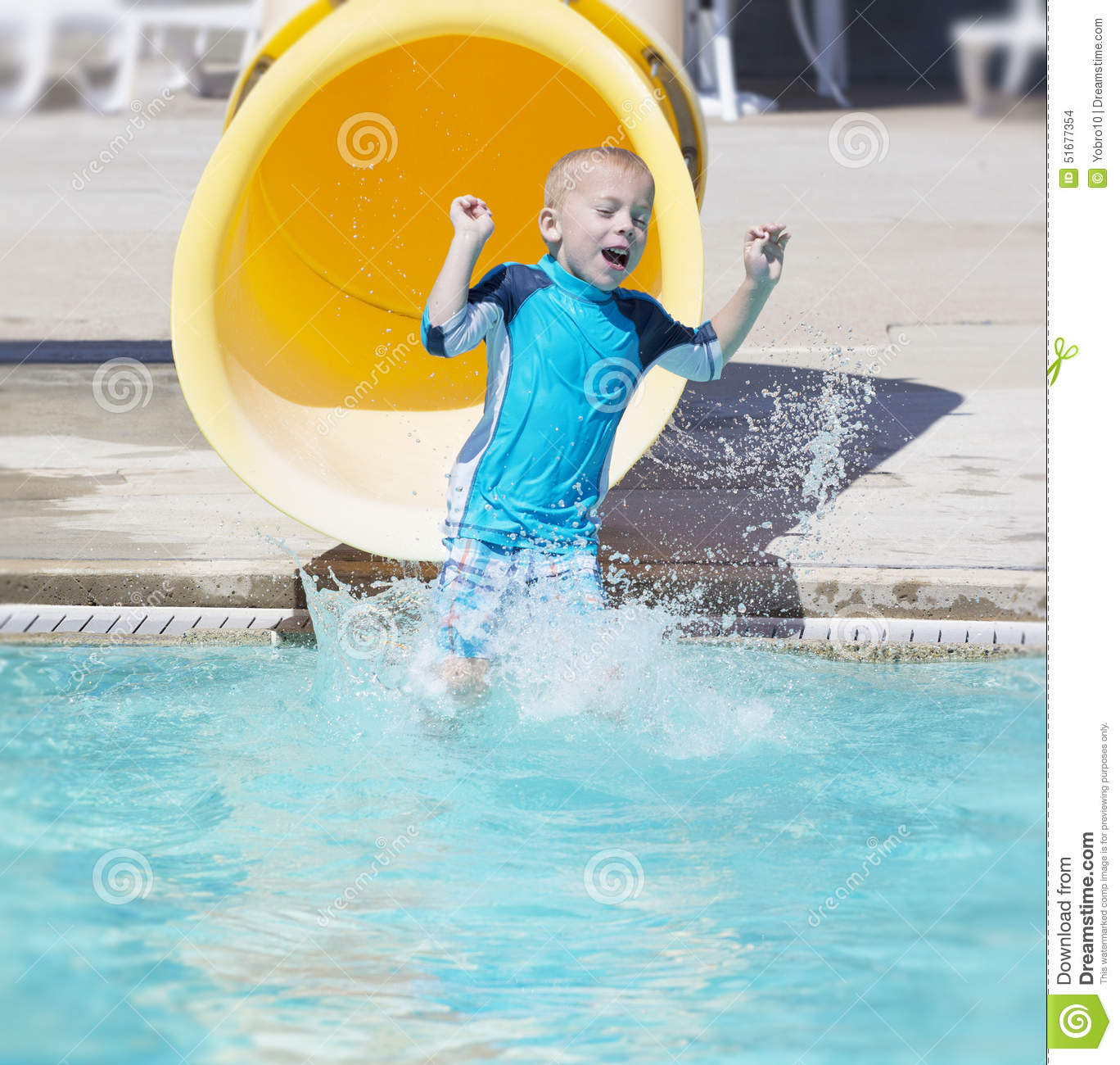 young boy sliding out of a yellow water slide stock photo