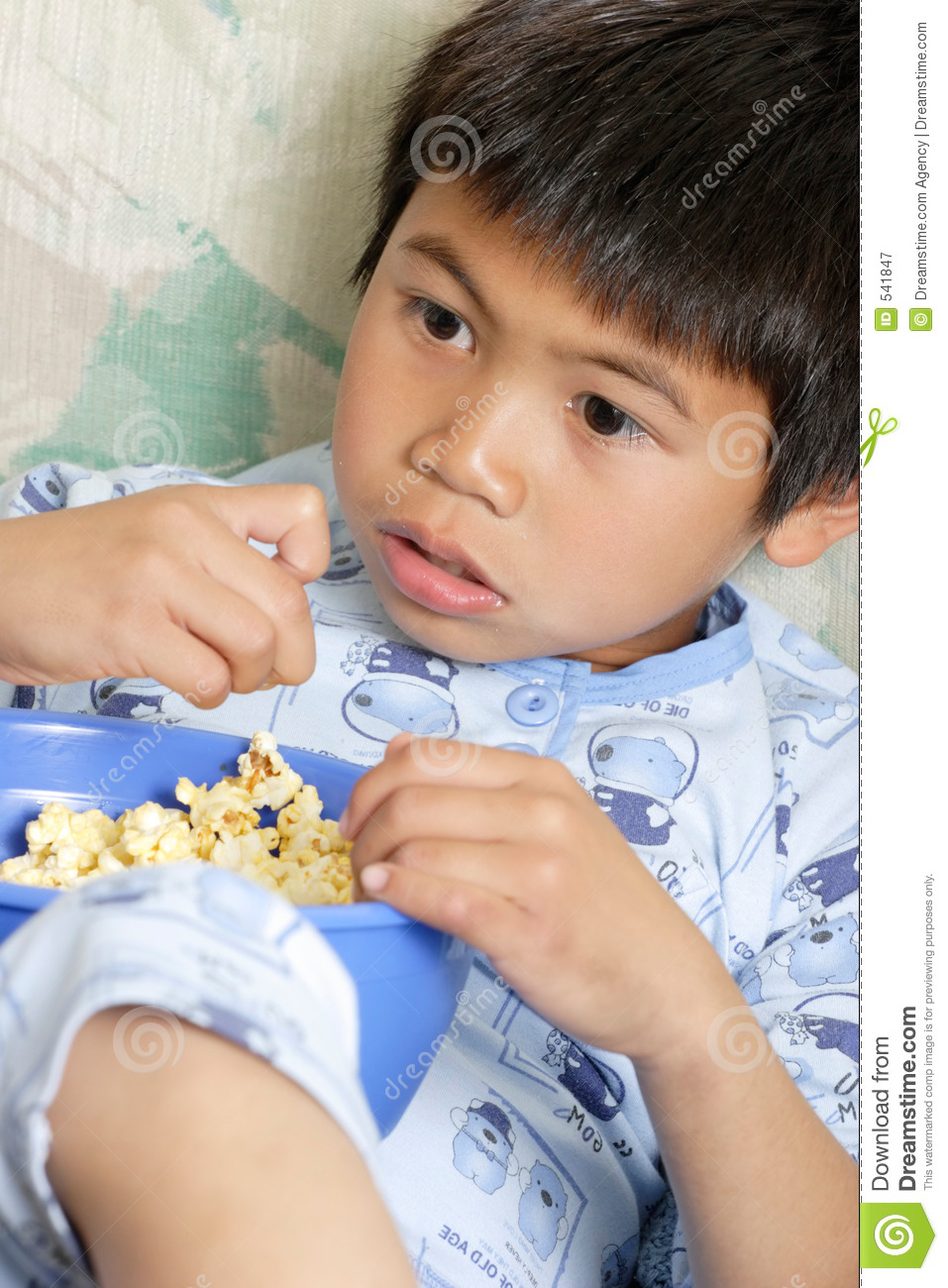 Young boy snacking on popcorn