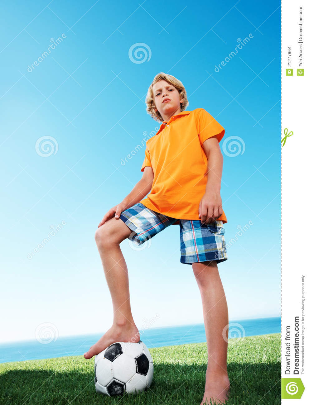 Young Boy Standing Confidently With Football Under Stock ...