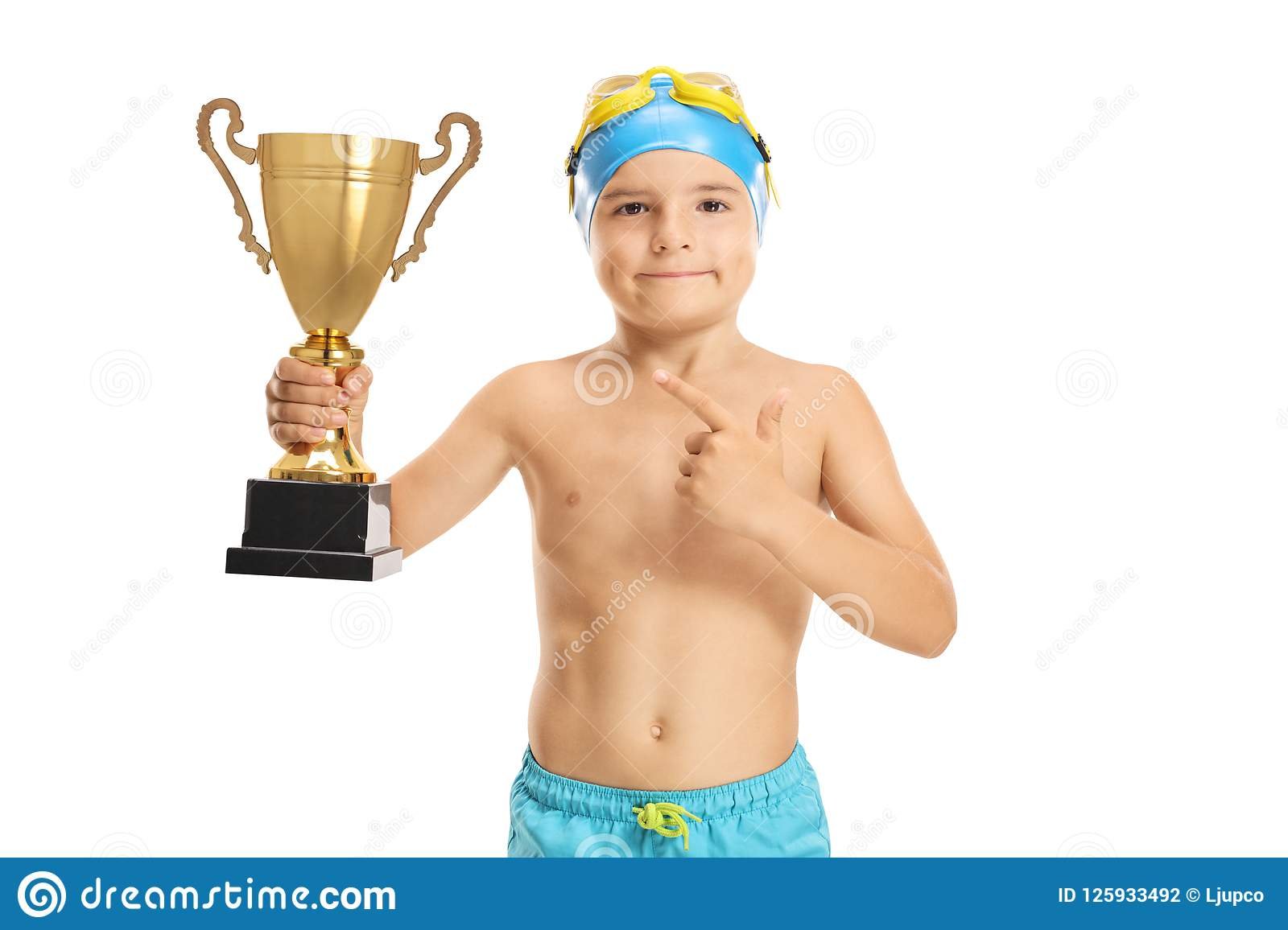 Young boy swimmer with a golden trophy pointing