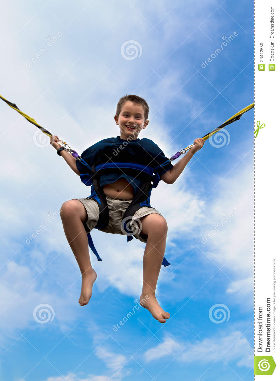 young boy swinging high air against cloudy blue summer sky harness attached to cables ropes beaming smile 33412550 young boy swinging high in the air stock photo image of handsome