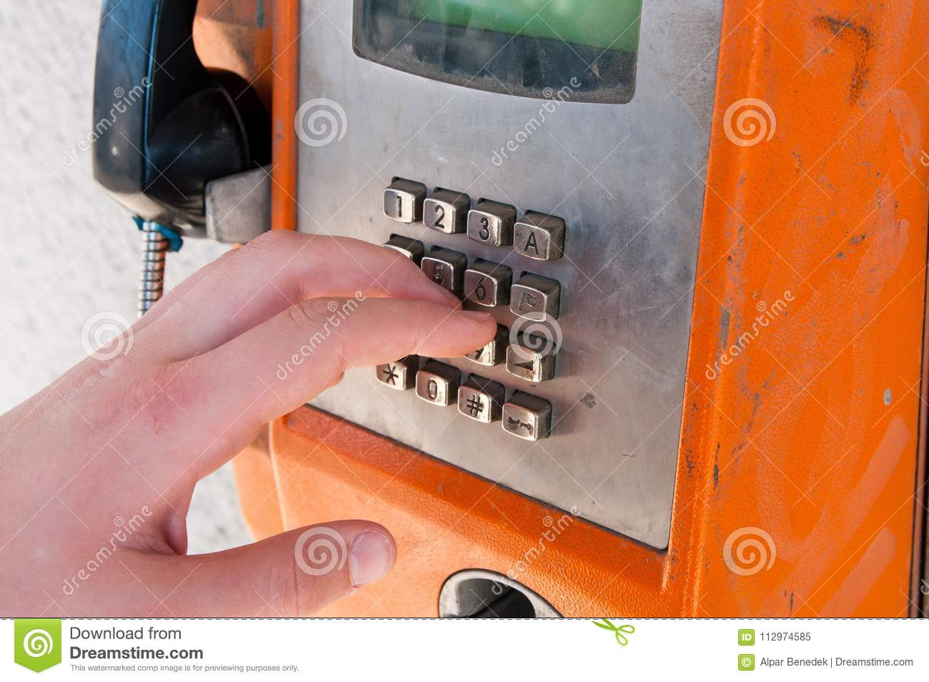 Young boy touching an old unused, unfunctional orange public phone