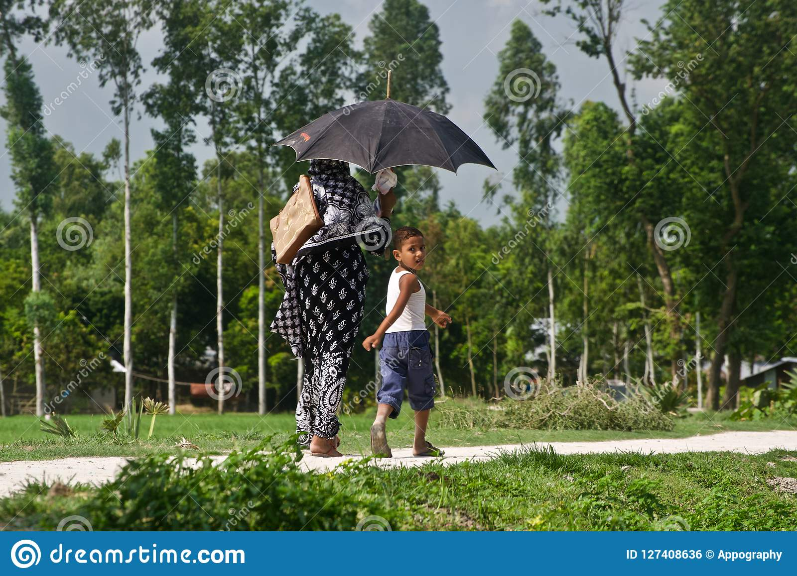 Young boy walking in a village road with his mother unique photo