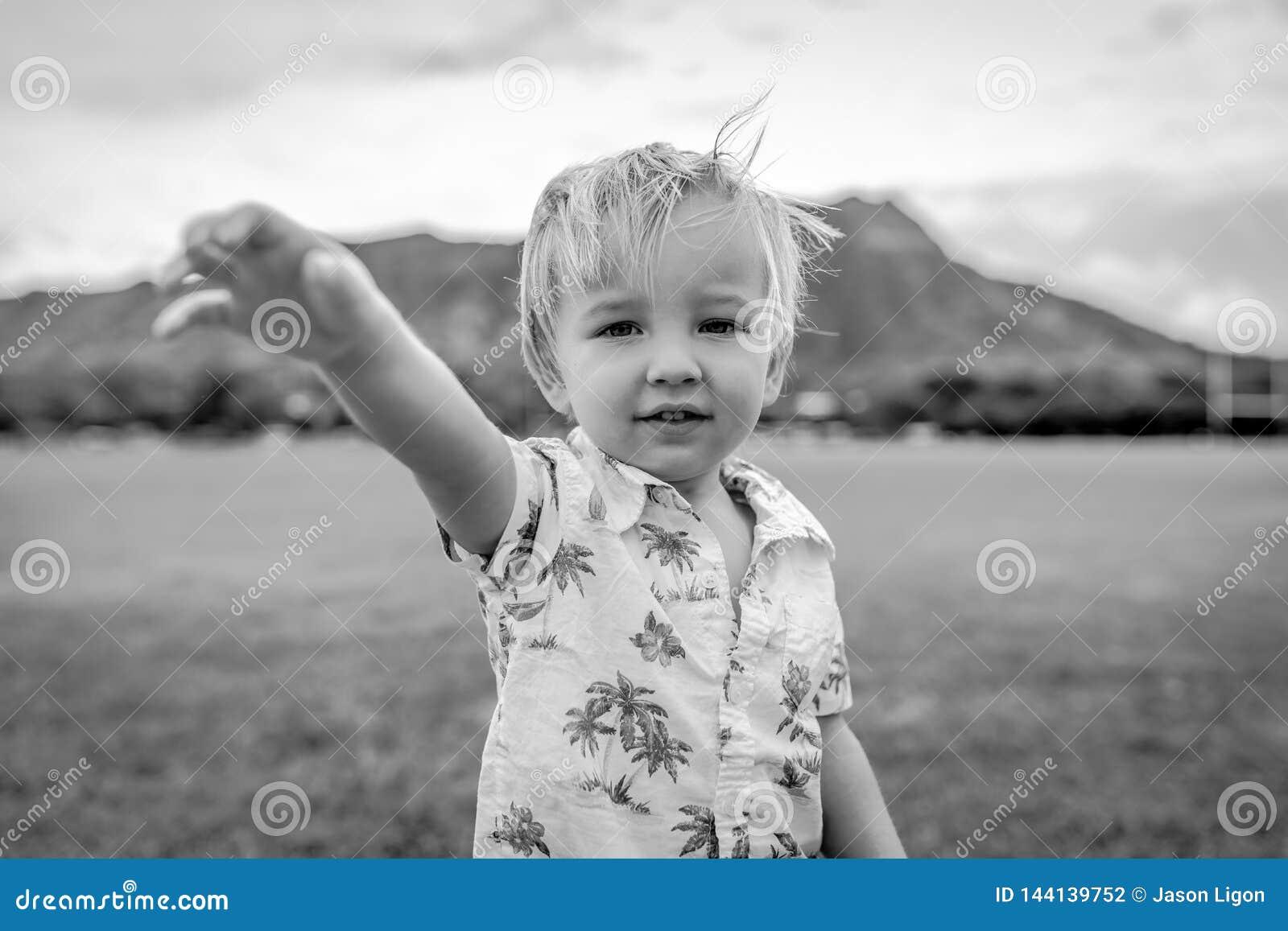 Young Boy Standing Wearing Aloha Shirt in Field