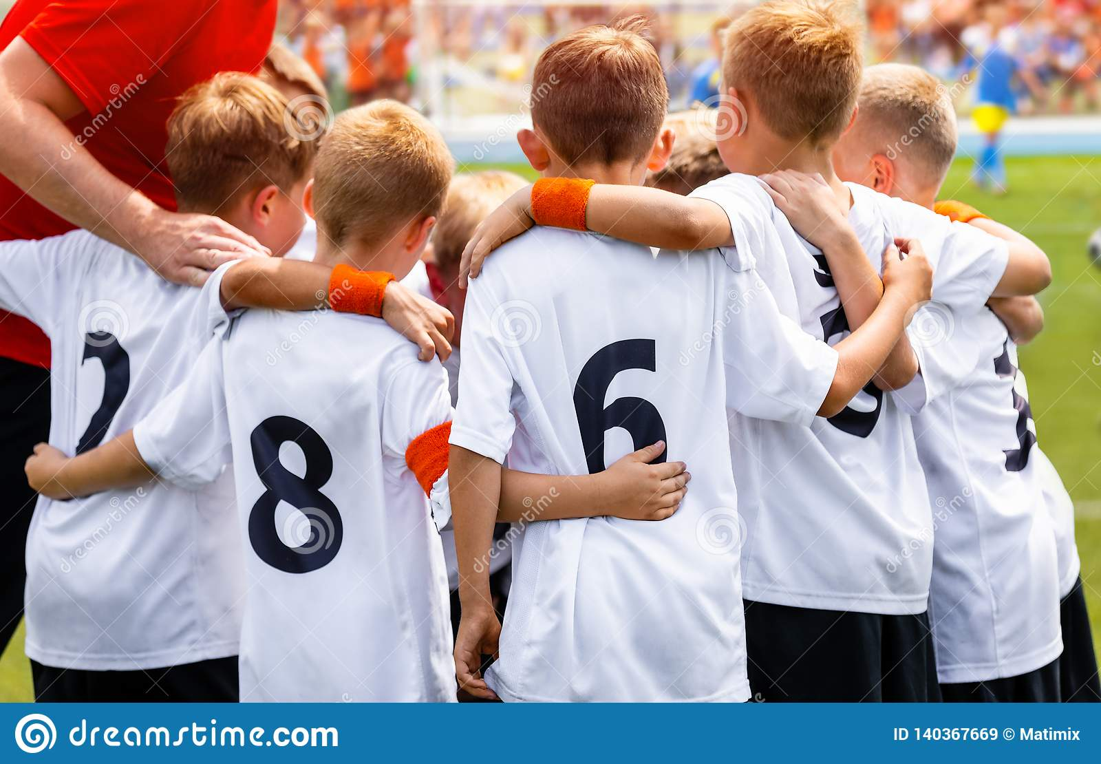 Young Boys In Football Team. Group Of Children In Soccer Team. School Football Coach's Pregame Speech