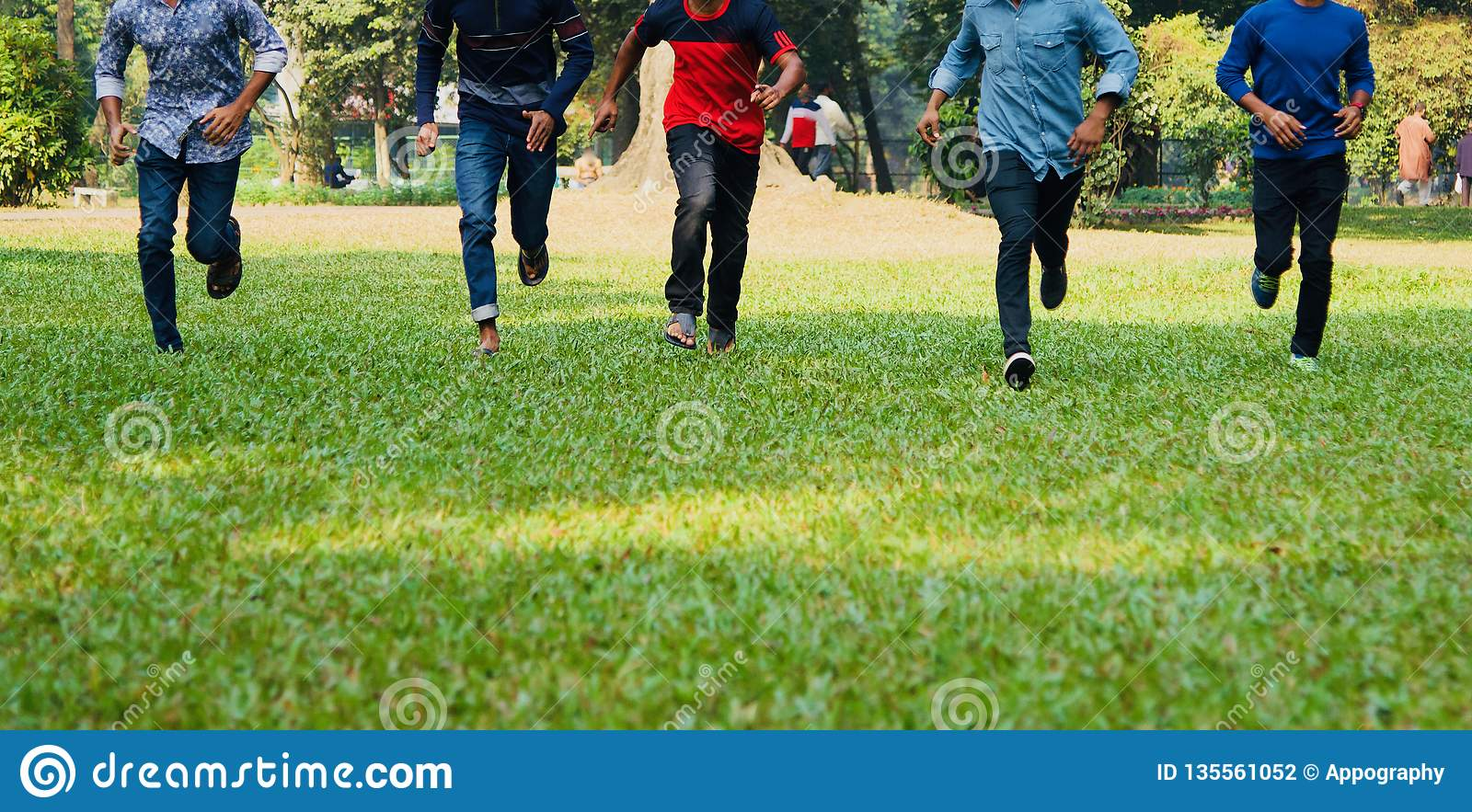Young boys running around a park