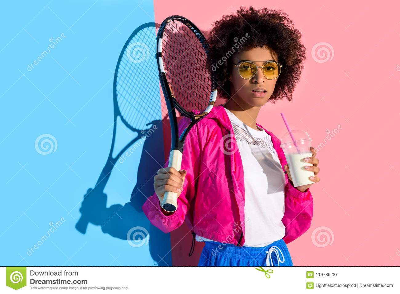 Young bright african american girl holding tennis racket and plastic cup with drink on pink and blue